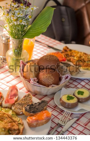 Breakfast with juice, omelette, sandwich, jamon and salmon/ appetizing  breakfast table arrangement with bouquet of daisies
