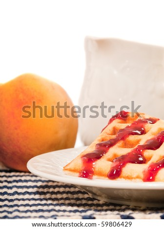 Breakfast with milk, waffles and a peach