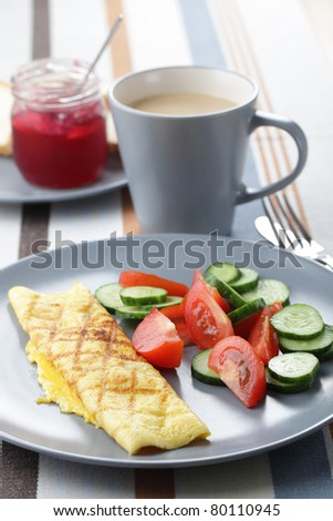 Breakfast with omelet roll, tomato and cucumber salad, and coffee