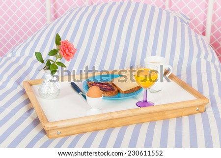 Breakfast with rose and bread on the bed for mothers day - stock photo