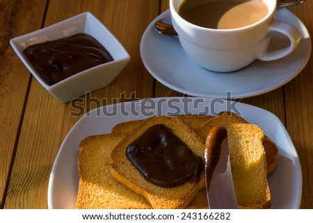 breakfast with rusks and cocoa cream in morning light - stock photo