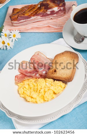 Breakfast with scrambled eggs and crispy bacon