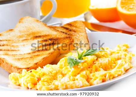 breakfast with scrambled eggs, toasts, juice and coffee - stock photo