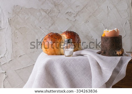 Breakfast with started eating soft-boiled egg with pouring yolk in wooden eggcup and home made bread on wooden chest with white cloth over white table. With plastered wall at background - stock photo