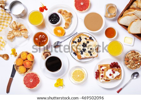 breakfast with toasts, fruits, jam, coffee and buns. top view