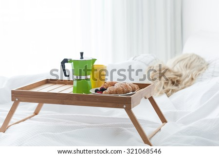 Breakfast wooden tray with coffee percolator and croissant on bed - stock photo