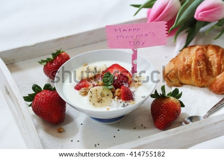 Breakfast yogurt bowl with strawberries and bananas served in a white tray with croissant Mother's day note and tulip flowers / Mother's day Brunch - stock photo