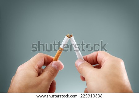 Breaking a cigarette in half concept for quitting smoking and healthy lifestyle - stock photo