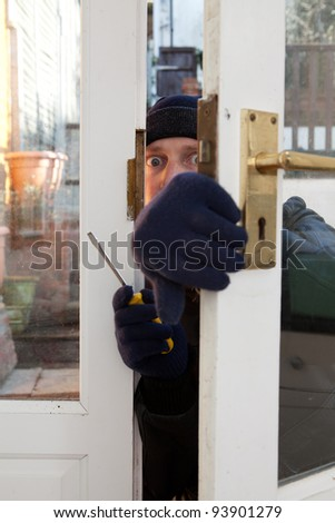 Breaking and entering home or house, Burglar with screwdriver force open door. Thief attempting to breach security - stock photo