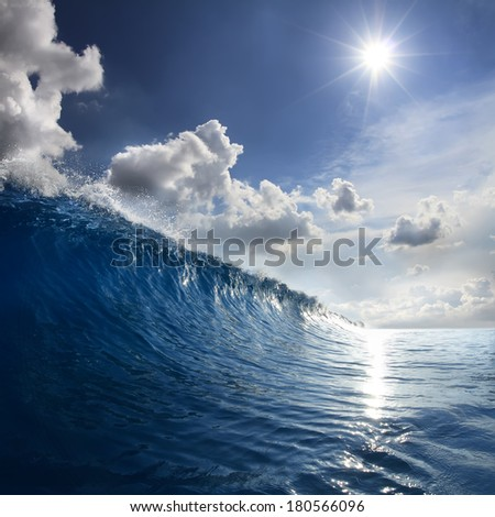 breaking blue ocean wave falling down at sunset time - stock photo