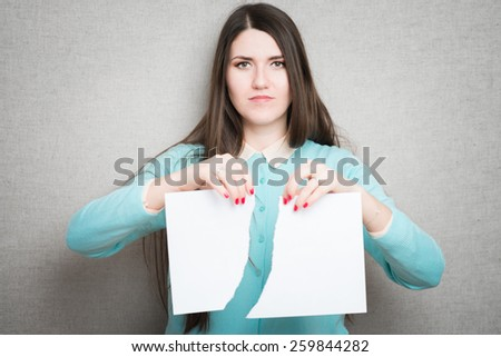 Breaking contract. Furious young woman tearing up paper  - stock photo