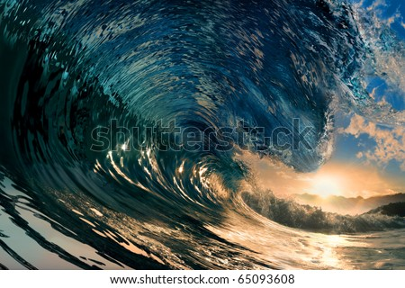 breaking ocean wave falling down at sunset time - stock photo