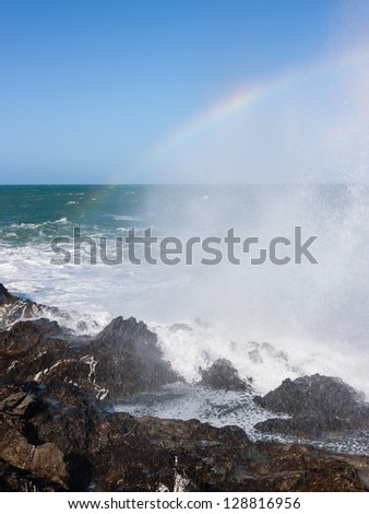 Breaking waves create a miniature rainbow in the spray - stock photo