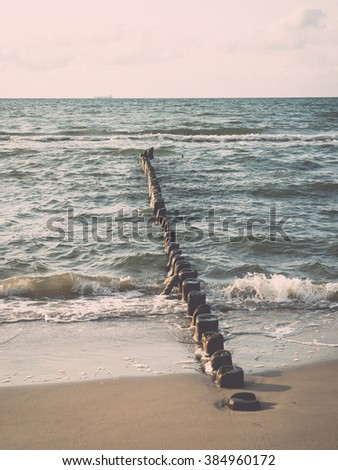 Breakwater of one row of wooden poles at the Sea coast. - vintage effect