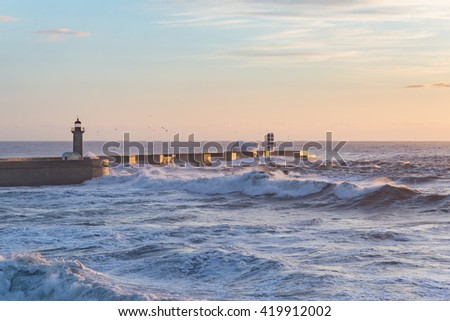 Breakwater pier coast sunset view dusk dawn ocean rough seas waves blue orange - stock photo