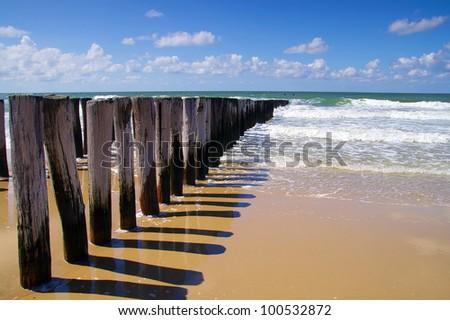 breakwaters on a sunny european beach, north sea in Domburg Holland - stock photo
