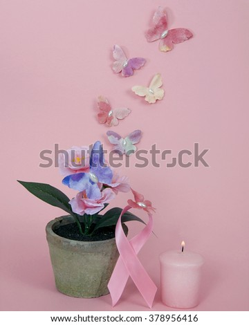 Breast Cancer Awareness, Burning light pink candle with primrose in pot next to pink ribbon with Breast Cancer Awareness loop, paper butterflies on flower ribbon and flying on textured pink background - stock photo