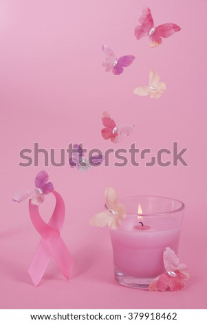 Breast Cancer Awareness ribbon loop with paper butterflies holding it up in the air, pink candle in glass burning and more paper butterflies flying up towards the ribbon more butterflies above - stock photo