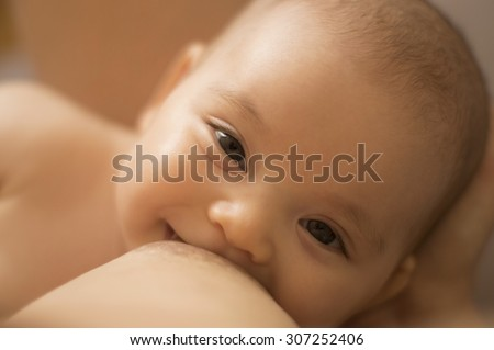 Breastfeeding baby. Smiling infant, looking in her mother's eyes, while breast feeding. Motherhood concept. Caucasian newborn face closeup. - stock photo