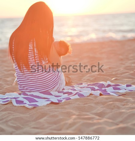 breastfeeding. mother feeding her baby in nature outdoors  - stock photo