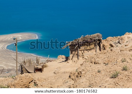 Breathtaking high mountain landscape of the Dead Sea shot at midday with the camp in the foreground - stock photo