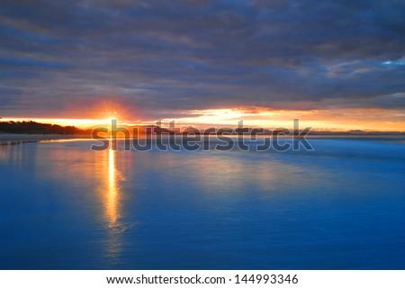 breathtaking sunset vibrant colors over Byron Bay beach, NSW, Australia - stock photo