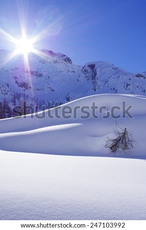 Breathtaking view of a mountain landscape with high mountain, snow, blue sky and clouds. - stock photo