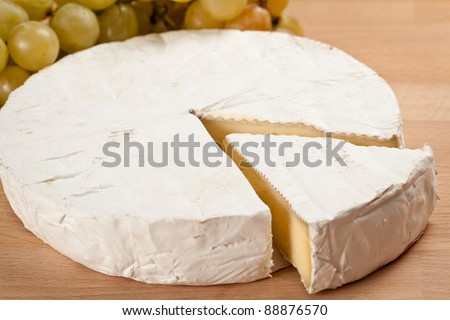 bree cheese with a slice off and grapes in isolated studio shot over wooden background