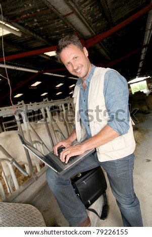 Breeder in barn with laptop computer - stock photo