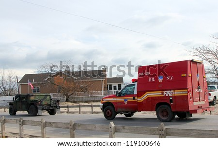 BREEZY POINT, NY - NOVEMBER 15:US National Guard and Fire Department vehicles moving to devastated area  in the aftermath of Hurricane Sandy on November 15, 2012 in Breezy Point, NY