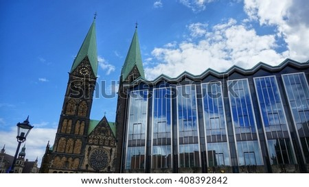 Bremen, Germany. Part of Parliament of Bremen and towers of Bremen Cathedral (German: 'Bremer Dom') on a sunny day. Partly cloudy sky mirrored in the huge glass front of the government building. - stock photo