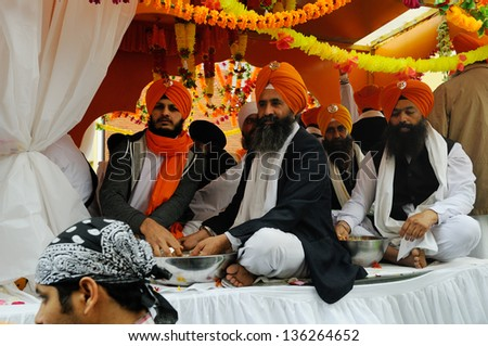 BRESCIA ITALY - APRIL 20: Sikh devotees offer food, as per tradition, at the Baisakhi (harvest) Sikh festival, on April 20, 2013 in Brescia - stock photo