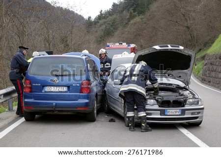 BRESSANONE, ITALY - MAY 8, 2015: Firefighters and Police Officer at work after hard collision between two cars on the road. First aid to injured motorist after car collision on May 8, 2015. - stock photo