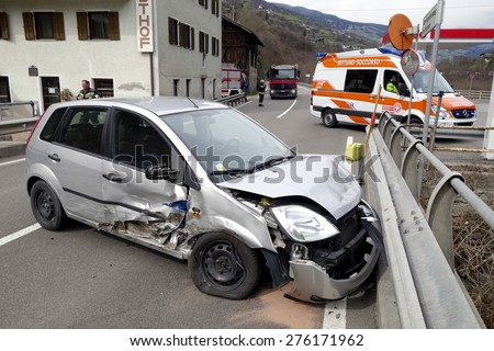 BRESSANONE, ITALY - MAY 8, 2015: Scene of a hard crash collision between two cars on the road. Paramedic with ambulance car after collision oh a mountain road on May 8, 2015. - stock photo