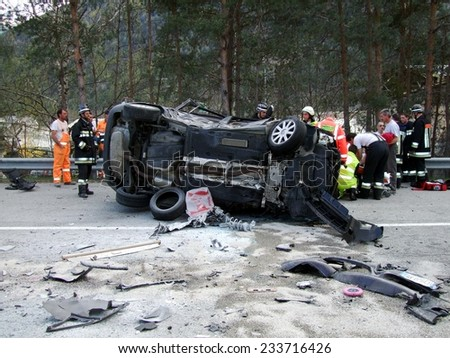 BRESSANONE, ITALY - NOVEMBER 27, 2014: Firefighters and Paramedics at work after a multiple collision between two cars on the road. Car crash turned upside-down in Bressanone on November 27, 2014 - stock photo