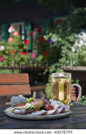 Brettljause - Austrian traditional plate of cold-cuts with self-made ingredient on old wood table - stock photo