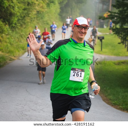 BREVARD, NC-MAY 28, 2016 -Joyous man runs in the White Squirrel Race with over 350 runners in Brevard, NC 2016.  Race is sponsored by Rotary Club of Brevard, NC - stock photo