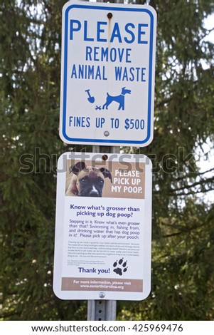 Brevard; North Carolina; USA - December 11; 2015:; Signs by the NC Dept. of Environment and Natural Resources urge pet owners to clean up their dog's poop for the health of the environment or be fined