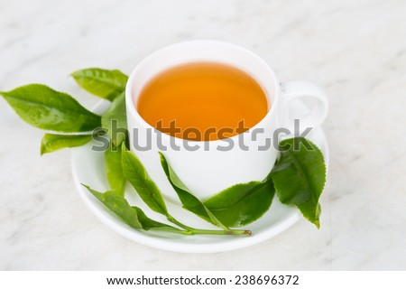 Brewed tea on table top, with freshly harvested tea as props. - stock photo