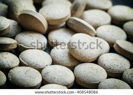 Brewer's yeast tablets on a dark background, selective focus, shallow depth of field - stock photo