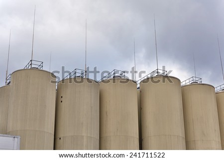 Brewery silos against cloudy sky - stock photo