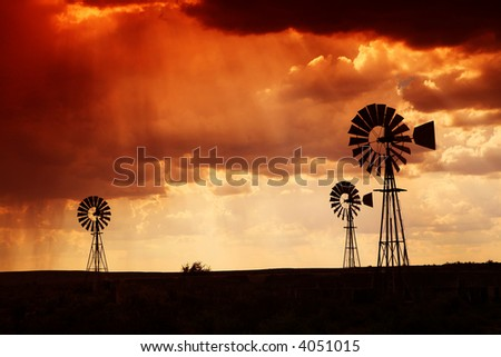 Brewing thunderstorm in the dessert area of the Karoo in South Africa just before sunset. Three wind pumps silhouetted against the skyline with sunbeams shining through the clouds. - stock photo