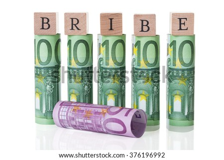 Bribe blocks arranged on rolled euro notes against white background