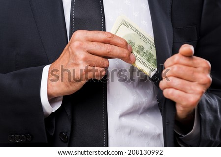 Bribe. Close-up of businessmen hiding money to his pocket