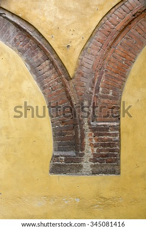 Brick arch in a yellow wall in Lucca, Italy - stock photo