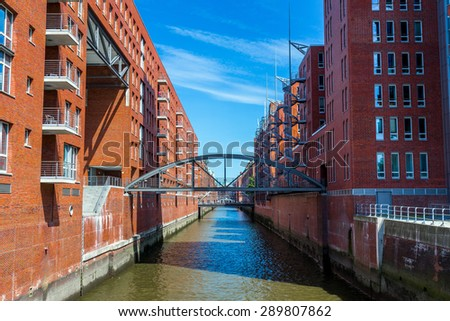Brick building along the river with a bridge and blue clouds sky background in Hafencity, Hamburg, Germany - stock photo