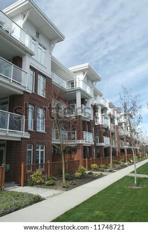 Brick Condominium Building With Sidewalk - stock photo