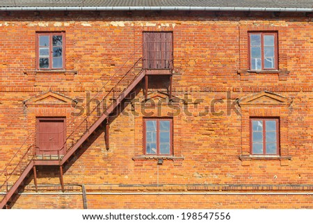 Brick facade with windows and stairs - stock photo