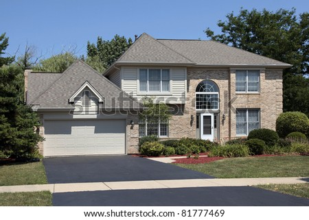 Brick home in suburbs with arched front windows - stock photo