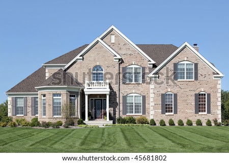 Brick home in suburbs with small white front balcony